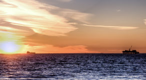 Off Shore Oil Rig at Sunset. Scenic landscape off shore oil rig and cargo ship at sunset stock photo
