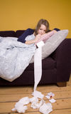 Off sick. Girl feeling poorly on a sofa under a duvet Royalty Free Stock Photos