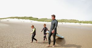 Off to go Surfing. Slow motion of two brothers and their dads walking down to the water`s edge to go surfing on their holiday stock video