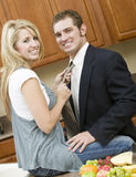Off to work. A woman fixing her husbands tie before he goes to work Stock Image
