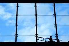 Silhouette of man carrying ladder Stock Photo