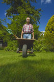 Off to work we go. A gardener pushing a wheelbarrow with tools, taken from a low viewpoint. Space for text on the green grass in front  of wheelbarrow Royalty Free Stock Photos