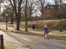 Off to work we go. Workers in Colonial Williamsburg head to their morning assignments near the Capital Building royalty free stock photo