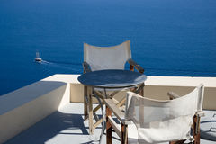 Off on a trip. Table and chairs with a view from the cliff over the sea, boat sailing off below Royalty Free Stock Images