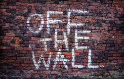 Off The Wall. Painted grafitti sign on an old brick wall Royalty Free Stock Photos