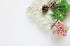 Διπλωμένη πλεκτή off-white μαλλιού πουλόβερ δώρων κιβωτίων πεύκων κώνων πράσινη ιουνιπέρων γιρλάντα φω'των κλαδίσκων χρυσή στον ξ στοκ εικόνες με δικαίωμα ελεύθερης χρήσης