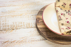 Off-white empty plate with red board on round cutting board, linen floral napkin Stock Image