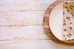 Off-white empty plate with red board on round cutting board, linen floral napkin,Provence style,kitchen interior Stock Image