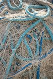 Off White Fishing Net with Blue Rope. Close up of a jumble of off white fishing net with off white, aquamarine and royal blue throughout the pile of netting Stock Image