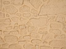 Off-white painted stone wall background texture. Off-white / yellow painted vintage stone wall background texture stock photo