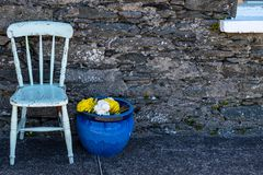 A off white painted wooden chair with a large blue ceramic plant pot with yellow and white flowers against an old stone exterior. Wall of a house, nobody in the stock image