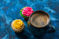 offee in blue cup, and delicious cakes on dark blue background Royalty Free Stock Photography