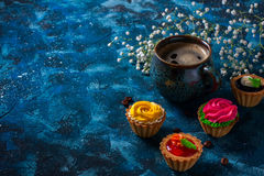 offee in blue cup, and delicious cakes on dark blue background Royalty Free Stock Image