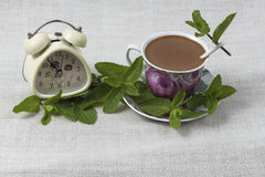 Ð¡offee break time. Cup of coffee with a spoon on the saucer, and an alarm clock on gray linen table cloth, decorated with green mint leaves royalty free stock photos