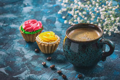 offee dans la tasse bleue, et gâteaux délicieux sur le fond bleu-foncé photos stock