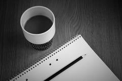 Offee mit Milch in der Kaffeetasse durch Weißbuch und Bleistift Stockfotografie