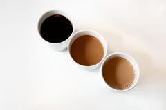 Offee-Schalen füllten mit Kaffee mit verschiedenen Mengen Milch Stockfoto