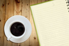 Offee and white sketch book on wood table. White cup of hot coffee and white sketch book on wood table Royalty Free Stock Photo