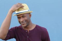 Offen und gesellig Hübscher junger afroer-amerikanisch Hippie, der Hand auf seinem Hut bei der Stellung gegen blauen Hintergrund  lizenzfreie stockfotos
