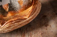 Offenbarungskuchen mit goldener Krone auf Holztisch backg Stockbilder