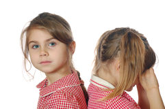 Offence. Two little girls sitting thier backs to each other Stock Image