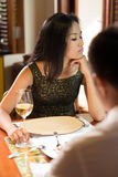 Offence. Vertical shot of an offended young women sitting at restaurant table with her boyfriend Stock Photography