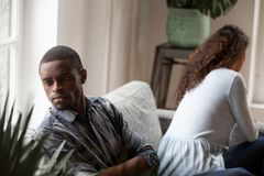 Offended African American couple sitting separately after quarre. L on couch at home, not talking, ignore each other, misunderstanding, men and women having royalty free stock photo