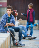 Offended boy and couple of teens apart on the street Royalty Free Stock Image