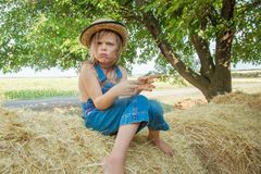 Offended child sits on a haystack stock image