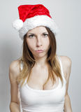 Offended christmas girl. Sad young girl in a christmas hat on white Royalty Free Stock Image