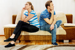 Offended couple sitting back to back on sofa.  Royalty Free Stock Photography