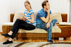 Offended couple sitting back to back on sofa.  Royalty Free Stock Photos