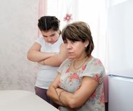 Daughter and mother after quarrel. Offended daughter next to mother after quarrel royalty free stock photo
