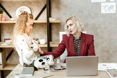 Sad frustrated blonde woman calming down her little daughter royalty free stock image