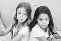 Offended feelings. Children offended keep silence. Relations sisters or best friends. Overcome relations issues. Childhood friendship. Friends sit back to back stock photos