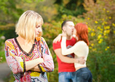 Offended girl. And young couple kissing and on a background (shallow Dof, focus on girl Royalty Free Stock Photo