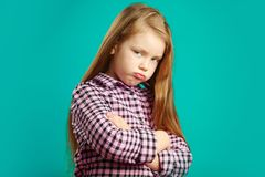 Offended girl with crossed arms at breast, inflated face from anger and dissatisfaction, expresses discontent, portrait. Of child in bad mood on blue Royalty Free Stock Images