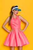 Offended Girl. Grimacing young woman in pink dress and sun visor posing with hand on hip. Three quarter length studio shot against yellow background Royalty Free Stock Photos