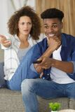 Offended girl sitting by boyfriend watching football match tv