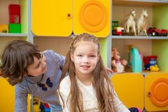 Offended girl tries to console another girl. one little girl looks in the face of another. Kindergarten Stock Photo