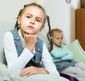 Offended girls sitting apart at home. Offended little girls sitting apart of each other after argue at home Stock Photo
