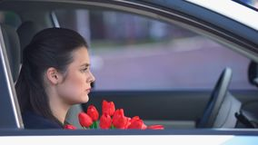 Offended lady with bunch of tulips sitting into car, male trying to apologize stock video