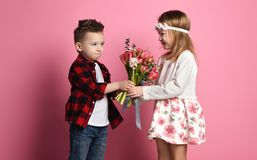 Offended little boy in blue jeans and red shirt hands bouquet of spring flowers to a little girl in dress and wreath of flowers. On pink background royalty free stock images