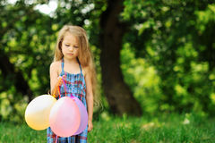 Offended little girl with baloons in a park Stock Photography
