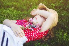 Offended little girl lies in the green grass and closed hands he Royalty Free Stock Photos