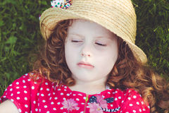 Offended little girl lies in the green grass. Toning to instagra Royalty Free Stock Images