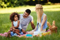 Offended little girl sitting with parents on picnic Stock Photography