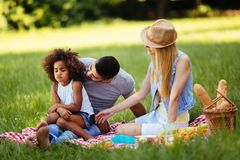 Offended little girl sitting with parents on picnic Royalty Free Stock Image