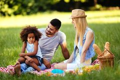 Offended little girl sitting with parents on picnic Royalty Free Stock Images