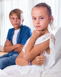Offended little girl and teenager indoors. Offended little girl and teenager boy sitting on couch at home Royalty Free Stock Images